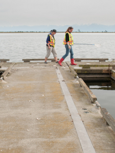 two people in rubber boots on a dock