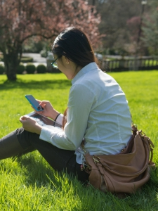 Picture of a student on her phone sitting in a grassy field