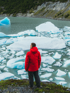 Man in red jacket in front of water with melting ice