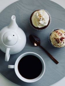 Photo of tea pot, tea cup, spoon and two cupcakes