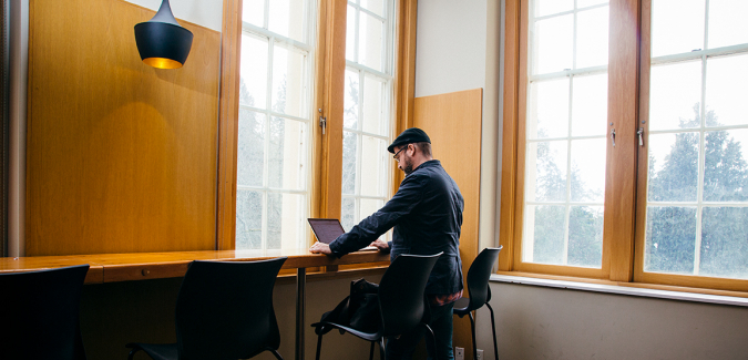 Person with laptop near windows