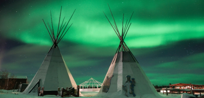 These lodges overlook Great Bear Lake and are lit by the northern lights