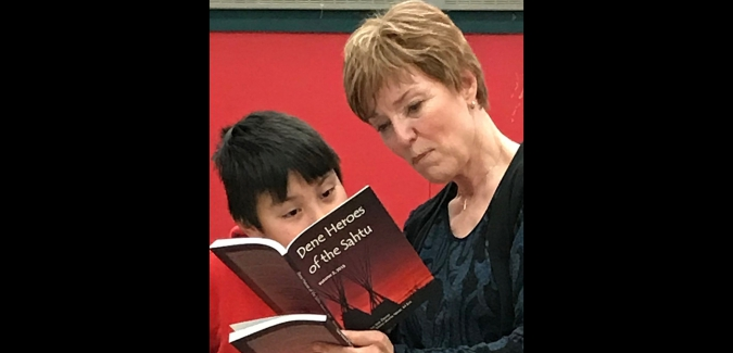 Mary-Anne Neal shows a young author where his story appears in the book
