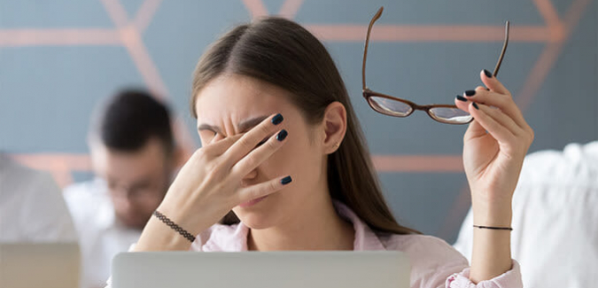 woman holding glasses in hand and rubbing her eyes