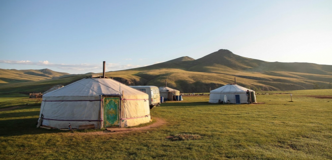 yurts with mountains in background